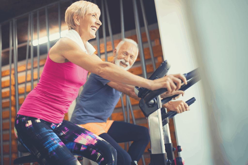 Older couple smiling on exercise bikes.