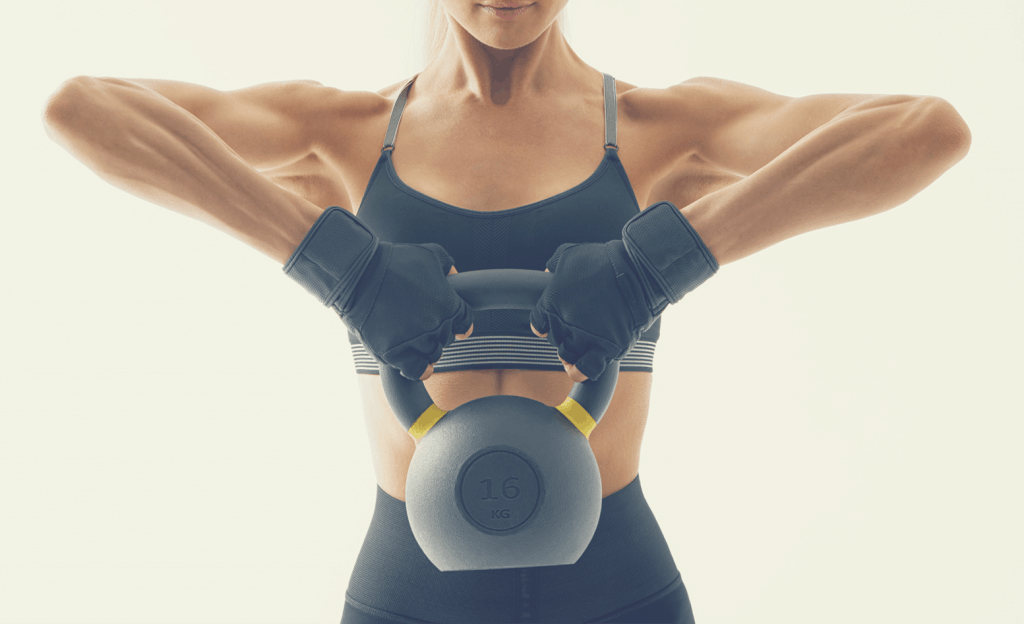 Fit woman doing kettlebell exercises.