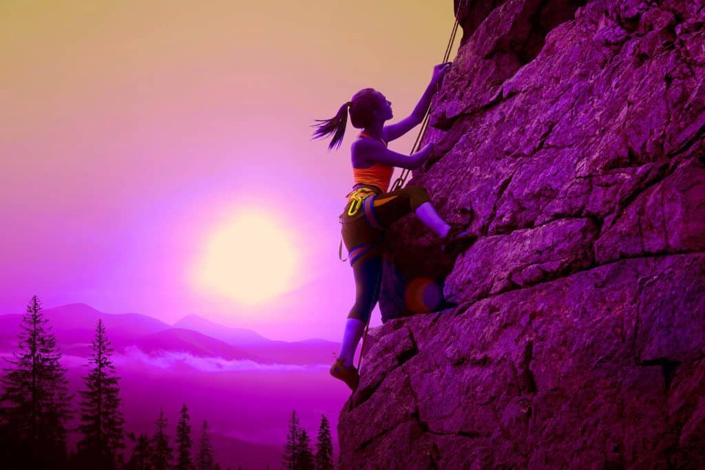 Woman rock climbing at sunrise - Best Vertical Climber featured image - heydayDo