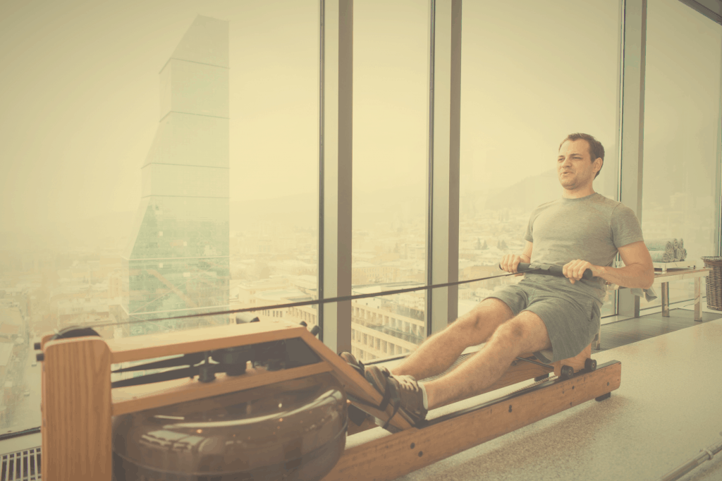 Man working out at home on a WaterRower machine