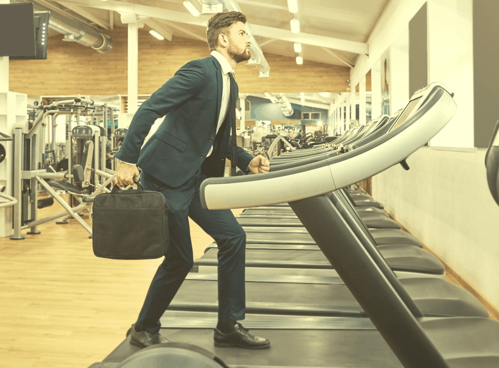 Man in business suit with briefcase climbing onto a treadmill as if to start work