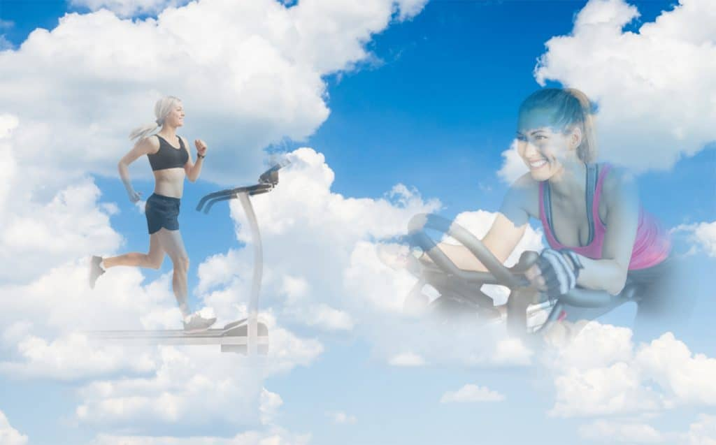 two women - 1 on treadmill 1 on a bike in the clouds smiling at each other