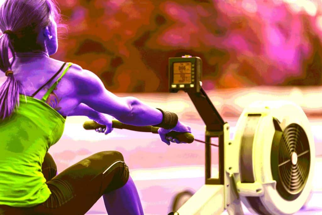 A woman toning all her major muscle groups during her rowing machine workout - heydayDo image