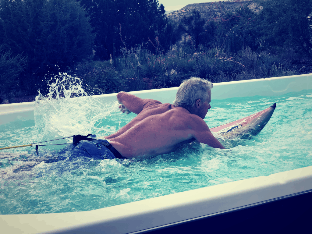 heydayDo author Greg Simon doing HIIT in a swim spa paddling on a surfboard