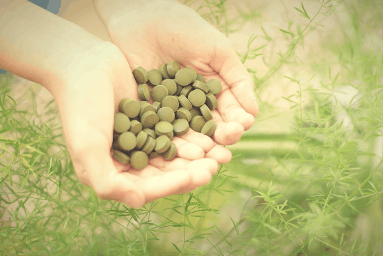 Two cupped hands holding pills made with an herbal proprietary blend and an asparagus fern in the background