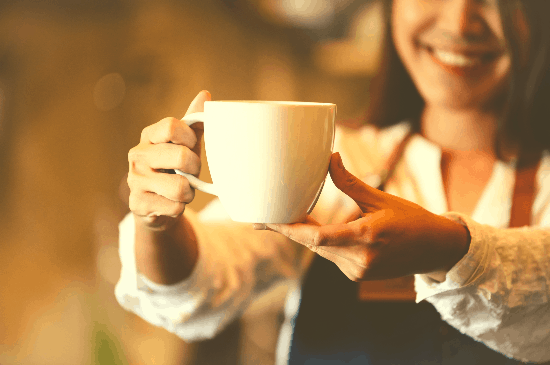 Smiling woman handing heydayDo author Greg Simon a cup of coffee
