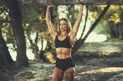 BODYBUILDING FEMALE WITH VERY LOW BODY FAT AND SIX-PACK ABS HOLDS UP A TREE LOG