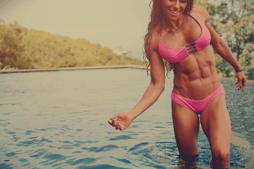 young woman with six-pack abs smiles & plays in a river