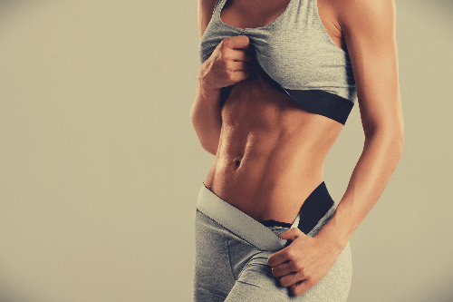 Fit woman showing off her well-developed six-pack abs