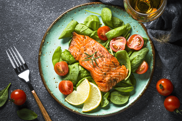 Grilled Salmon on spinach leaves with tomatoes, part of the heydayDo skinny fat diet