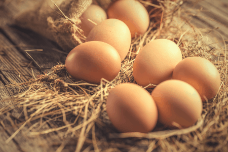 Brown eggs on wooden table with straw