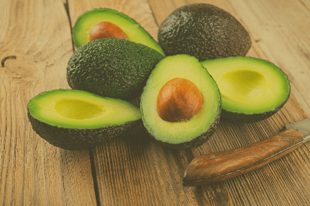 Halved avocados on wooden table