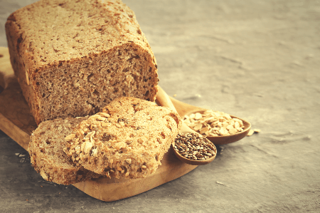 whole grain bread loaf shown with spoons of flax & sunflower seeds