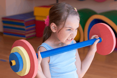 little girl making a grimacing face as she lifts a toy barbell