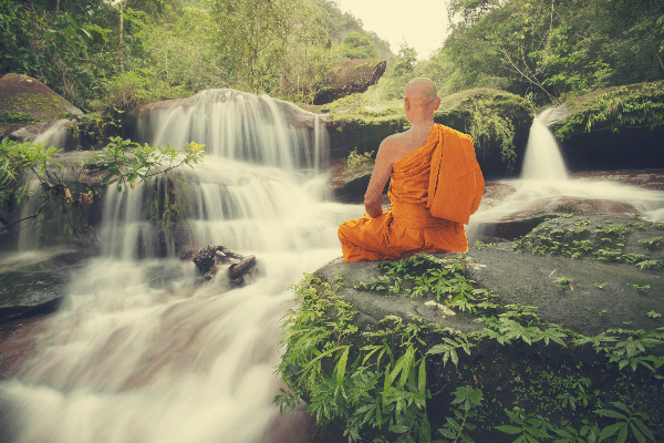 Buddhist monk sitting by waterfall mentally rejuvenating by taking a week off from the gym