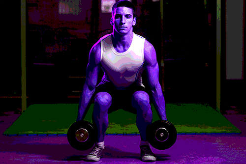 Muscular young man at the bottom of the dumbbell squat movement with thighs parallel to the floor - heydayDo image