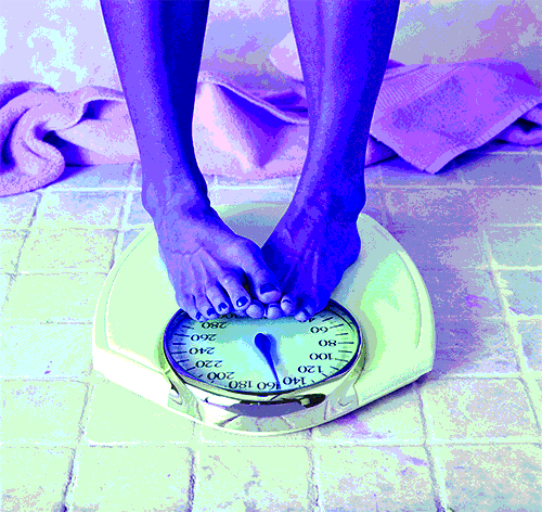 Woman's feet scrunching as she stands on bathroom scale looking at her weight - heydayDo image